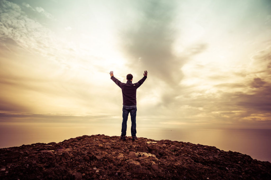 Man Standing on Hill with Hands Raised to Sky