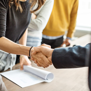 Two People Shaking Hands of Table and Papers